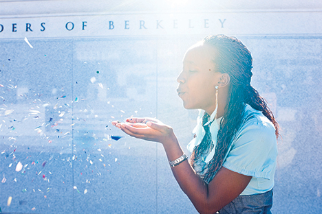 Student blowing confetti with Berkeley sign on building in background