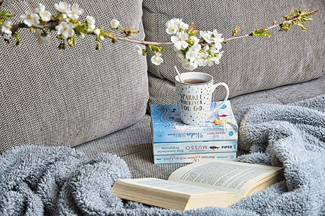 Photo of stack of books and cup of tea and flowers