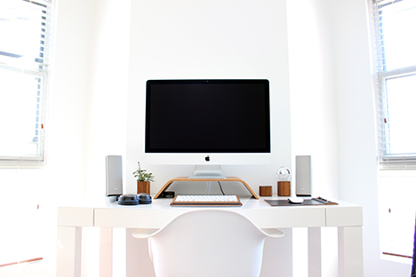 Photo of Apple desktop computer in a white room with white furniture
