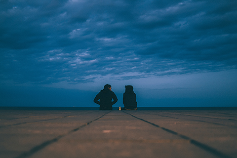 Photo of two people sitting on pier near water and dark blue sky