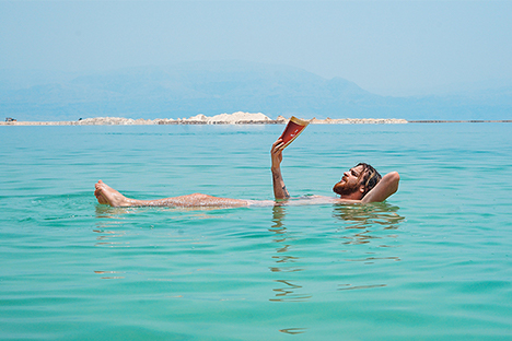 Photo of man reading while floating in water