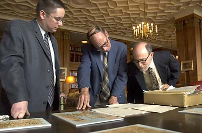 Berkeley scholars examine one of the recently returned papyri