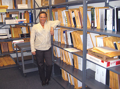 Laurie Roach with shelves of printed dissertations