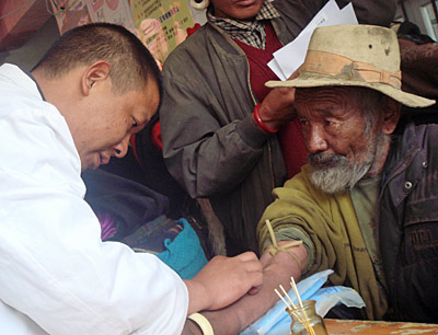Chinese technician collecting blood from Tibetan man