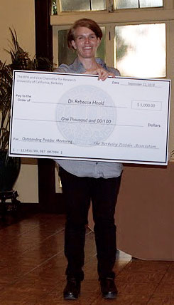 Postdoc holding replica of check