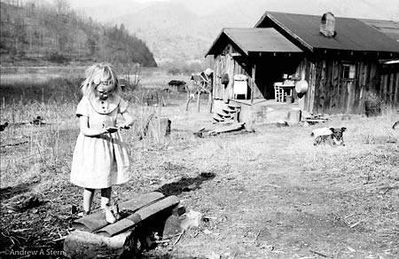 A young girl fingerpainting outside her Appalachian home