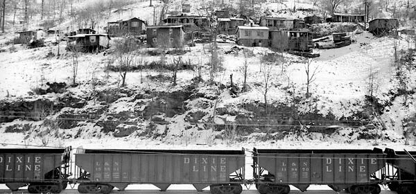 Humble houses on an Appalachian hillside, with coal train in foreground