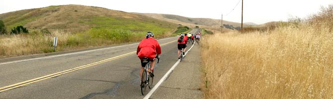 Cyclists in red climb a stretch of highway