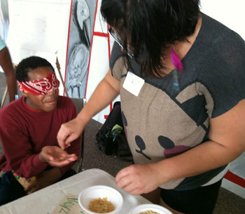 Magnolia Project volunteer Ingrid Villarreal  serves Trey, 13, different types of cereal in a blindfolded taste test.