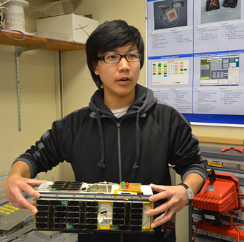 Student Jerry Kim with CINEMA nanosatellite.